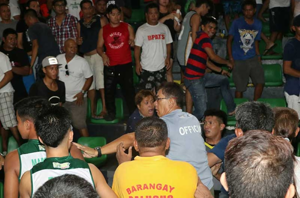 PAMPANGA. A basketball official tries to shield a referee from an angry Apalit crowd after a controversial call which resulted in a one point win for Team Guagua during Thursday's NLEx Basketball Cup Intertown at the Bren Z. Guiao Convention Center Convention Center. (Chris Navarro)