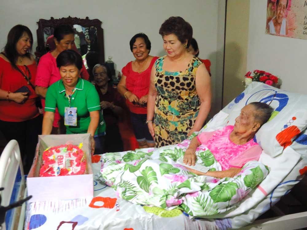 """Birthday gift. Si Lapulapu City Mayor Paz Radaza (tuo) nihatag og birthday gift sa laing Oponganon centenarian nga si Esther """"Mama Nene""""  Roldan sa  Brgy. Looc kagahapon. (Allan Cuizon)"""