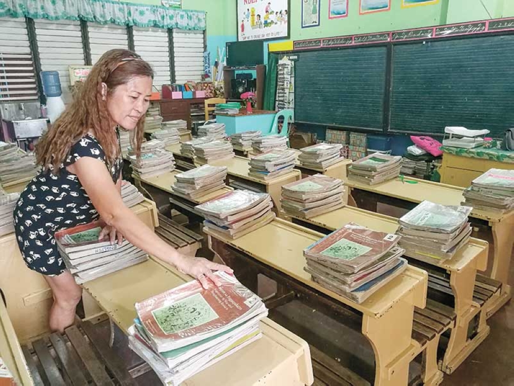 BRIGHT AND EARLY . A day ahead of the opening of classes in public schools, stacks of textbooks are ready for this teacher's pupils this school year. (SunStar photo / Arni Aclao)