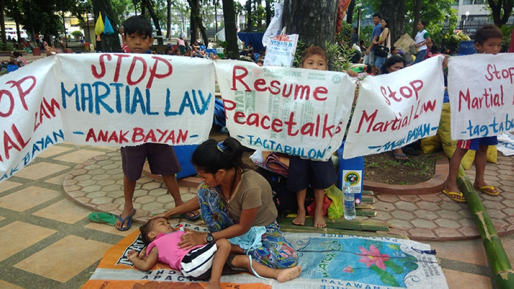 CAGAYAN DE ORO. A mother checks the temperature of her son's fever as other children hold placards calling for the resumption of peace talks between the government and communist rebels. The children are among displaced individuals affected by the skirmishes between government troops and communists in Sitio Camansi, Banglay, Lagonglong, Misamis Oriental. (Alwen Saliring)