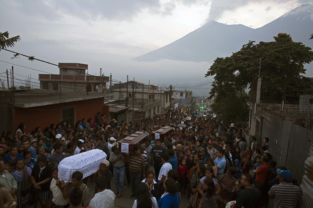 GUATEMALA. People carry the coffins of seven people who died during the eruption of the Volcan de Fuego, which in Spanish means Volcano of Fire, in the background, to the cemetery in San Juan Alotenango, Guatemala, Monday, June 4, 2018. Residents of villages skirting the volcano began mourning the dead after an eruption buried them in searing ash and mud.(AP)