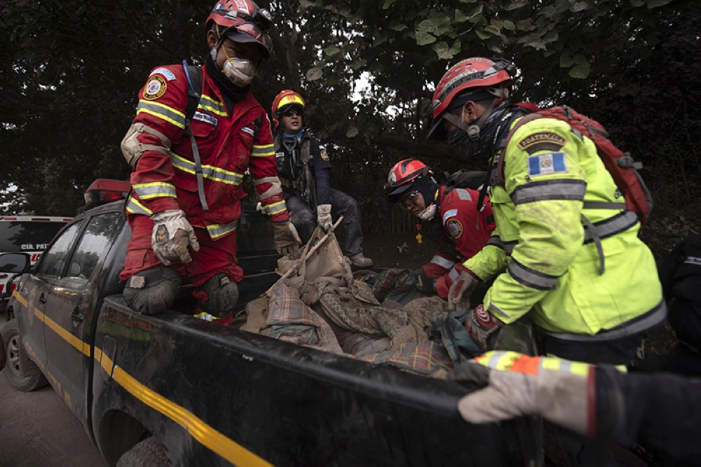 GUATEMALA. Firefighters transport a body recovered near the Volcan de Fuego, or