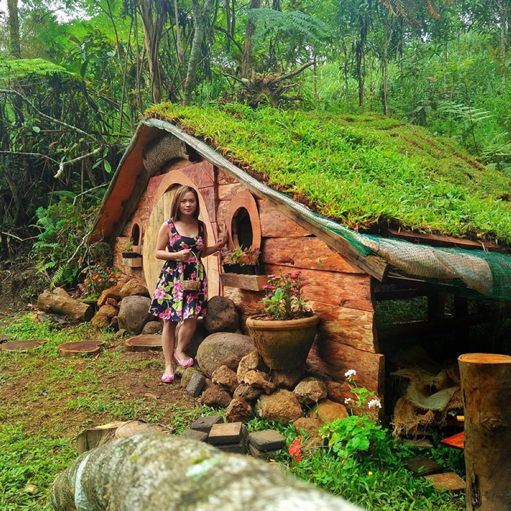 BUKIDNON. Axa Jojo Sulatan, a financial adviser of AXA Philippines, takes a photo with the DIY Hobbit house built by Benjamin Torregosa Maputi Jr. located within Mt. Kitanglad Agro-Eco Farm in Malaybalay City, Bukidnon. (Photo from Axa Jojo Sulatan's Facebook account)