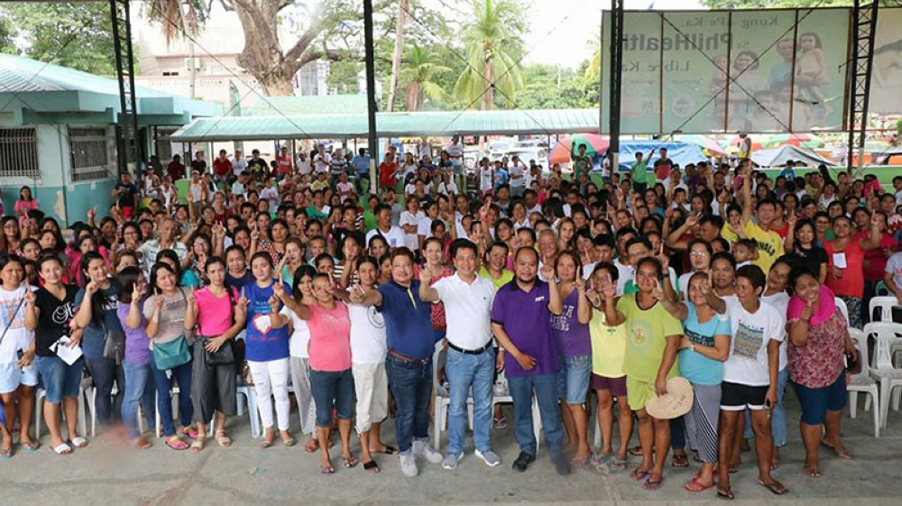 """APALIT. Mayor Peter Nucom, Councilor Kenneth Nunag and Rommel Casapao, Project Development Officer II of DSWD-Central Luzon flash the """"ToPNotch sign"""" together with 1,180 residents who benefitted from the P3.2 Million """"Cash for Work"""" program for Climate Change Mitigation and Adoptation during Thursday's orientation. (Chris Navarro)"""