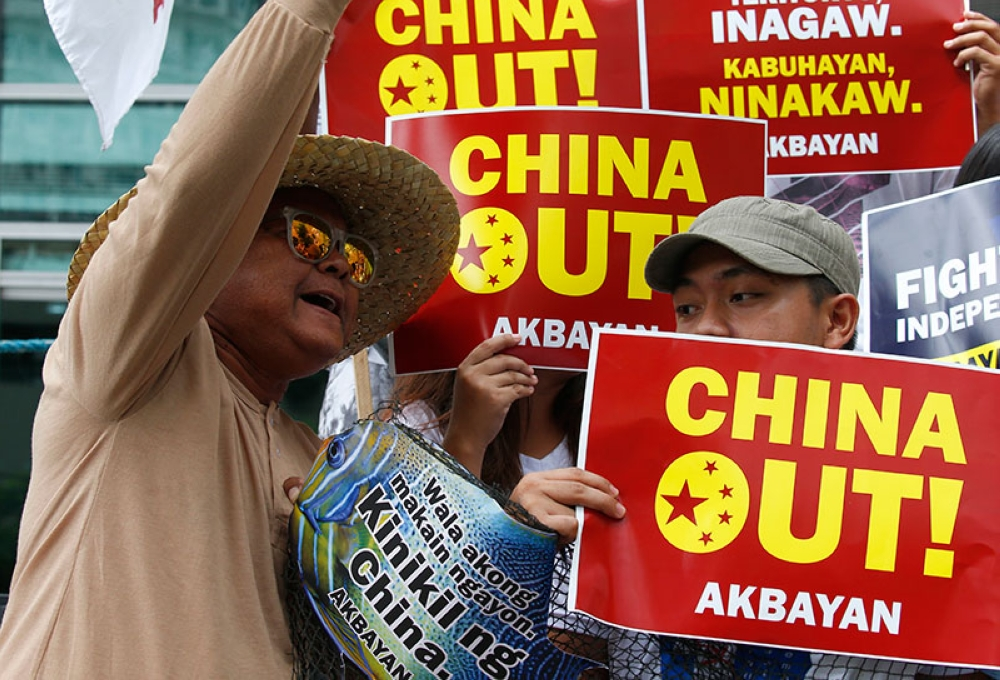 MANILA. Protesters shout slogans while displaying placards during a rally at the Chinese Consulate in the financial district of Makati city to protest alleged continued seizure of catches of Filipino fishermen at a disputed shoal in the South China Sea despite a protest by the Philippines following an earlier incident Monday, June 11, 2018. (AP Photo)