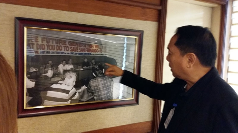 PAMPANGA. Save San Fernando prime mover Levy Laus points to a framed photo of a meeting where volunteers gathered to make a crucial decision in the aftermath of Mt. Pinatubo's eruption 27 years ago. (JTD)