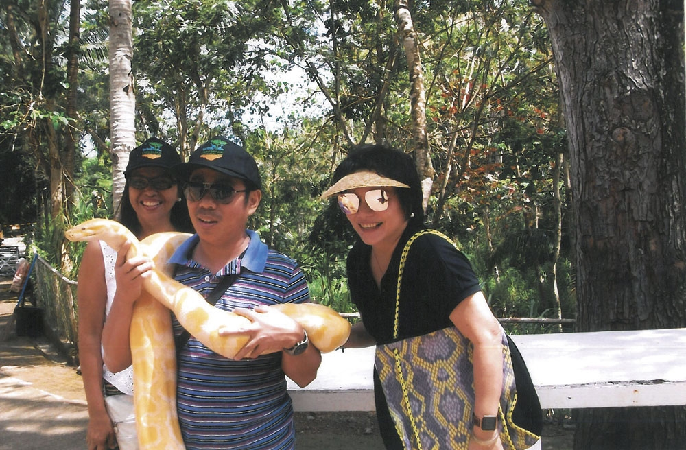 Marget Villarica (right) poses with an albino Burmese python.