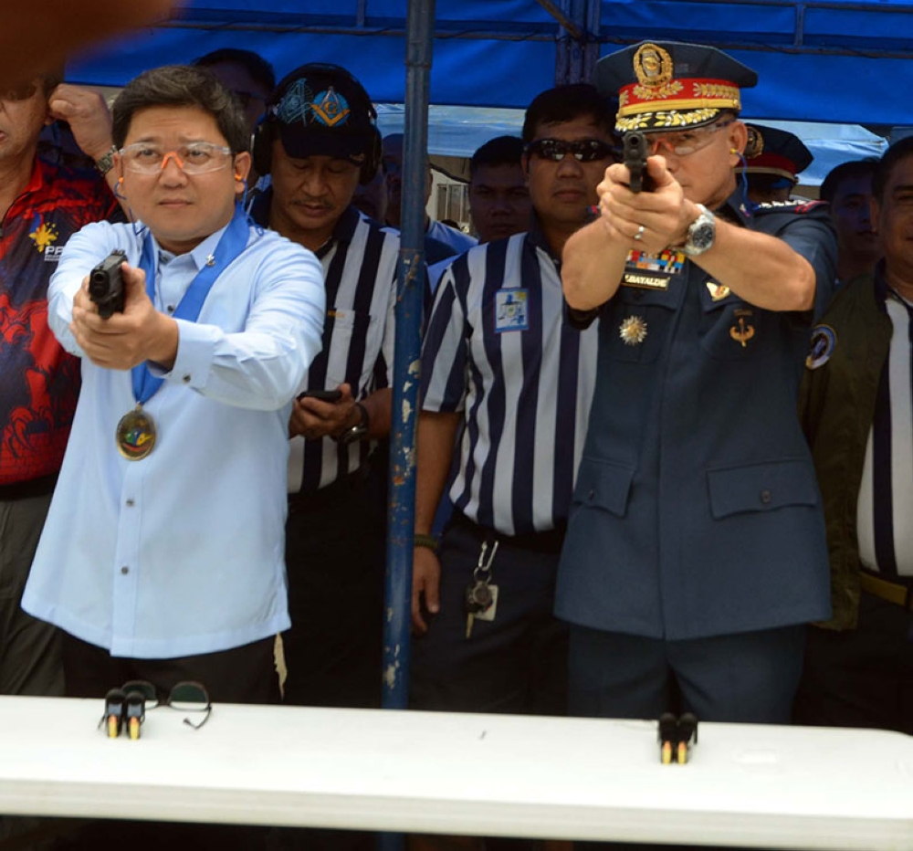 MANILA. Quezon City Mayor Herbert Bautista (left) and PNP chief Oscar Albayalde test fire the guns given by the city government to the police on Thursday, June 14, 2018. (Alfonso Padilla/SunStar Philippines)
