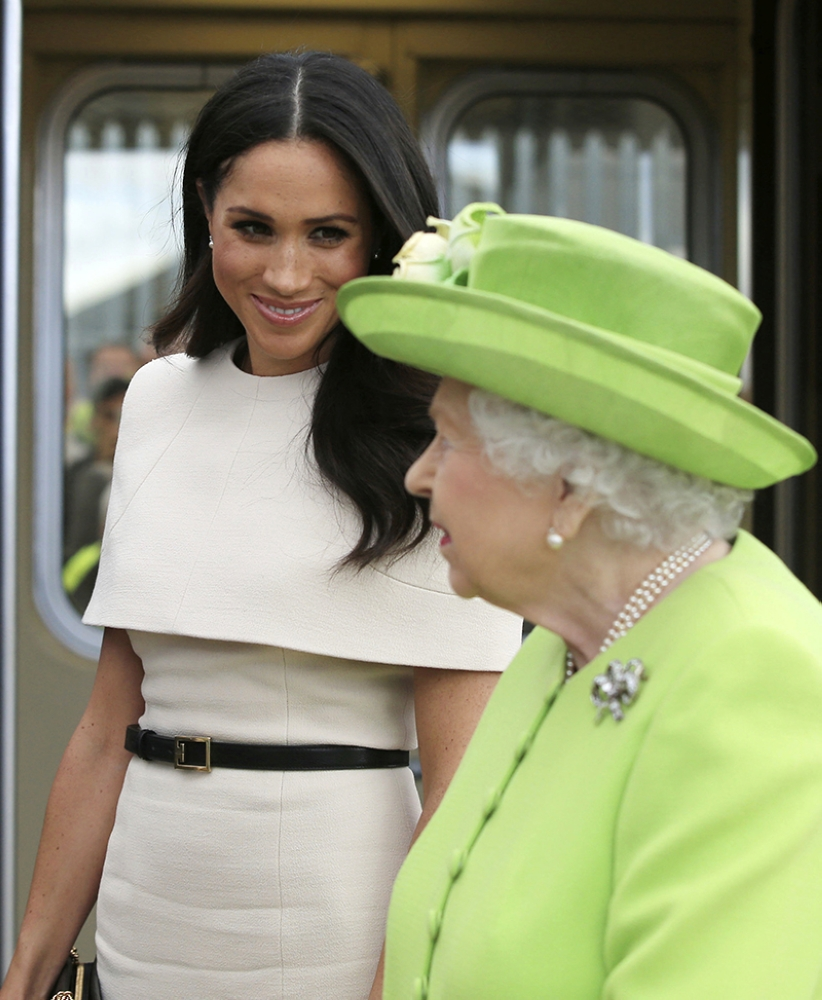 ENGLAND. Britain's Queen Elizabeth II and Meghan, the Duchess of Sussex arrive by Royal Train at Runcorn Station, north west England, Thursday June 14, 2018. (AP)