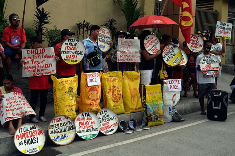 MANILA. In this photo taken on May 22, 2018, protesters display placards calling for higher buying prices for palay and lower prices of rice at the gate of the National Food Authority central office. (File Photo)