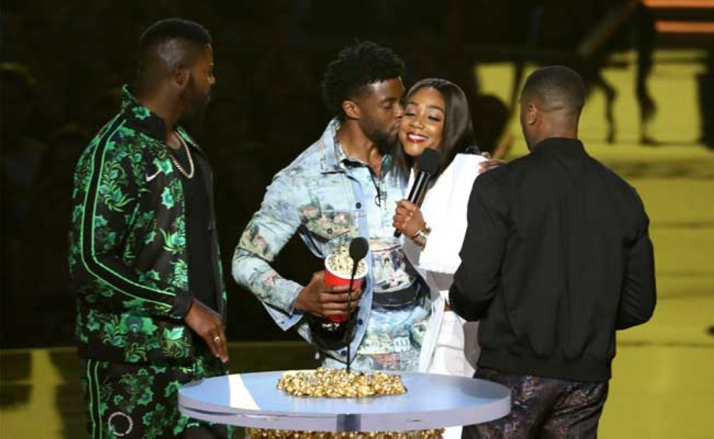 "Black Panther himself, Chadwick Boseman (second from left), accepts the popcorn for best movie for ""Black Panther,"" and kisses host Tifanny Haddish as additional incentive. They are flanked by ""Panther"" co-stars Winston Duke (left) and Michael B. Jordan. (AP Foto/Matt Sayles)"