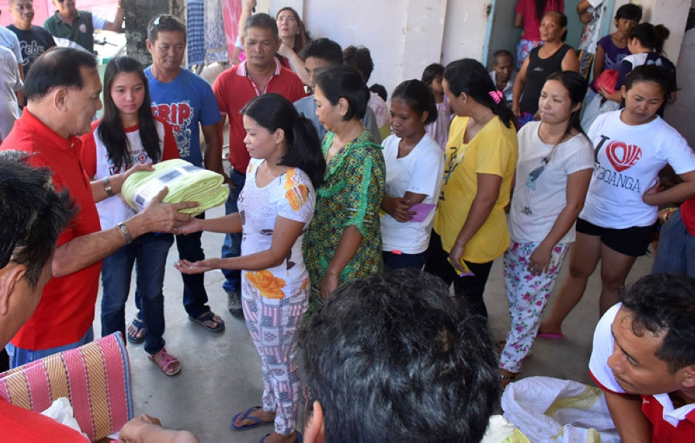 ZAMBOANGA. First congressional district office photo handouts shows Rep. Celso Lobregat, as Philippine red Cross governor, leads the distribution of relief assistance to the 22-family fire victims in San Jose Gusu village on Saturday, June 23. (Bong Garcia)