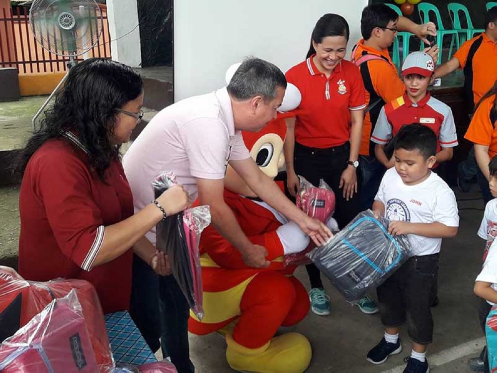 PONTEVEDRA. Provincial Agrarian Reform Program Officer II Lucrecia Taberna (left) and Mayor Jose Benito Alonso (second from left) lead the distribution of school supplies to at least 200 pupils at Barangay Don Salvador Benedicto in Pontevedra Wednesday, June 27. (Contributed Photo)