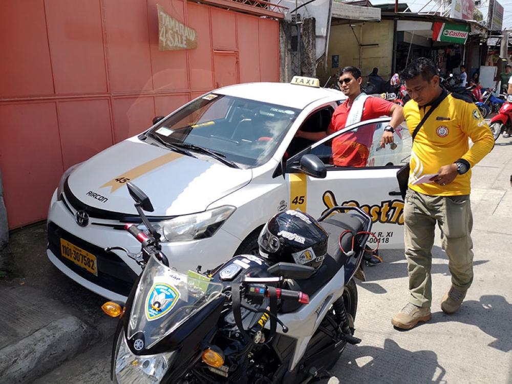 DAVAO. Usa ka taxi driver, nangandam nga tanggalon iyang gi-drayban nga taxi human kini gi-isyuhan og ticket sa iyang pag-parking sa sidewalk sa Barangay Ma-a, Davao City Lunes sa buntag. Ang mga personahe sa Davao City Traffic and Transport Management Office (CTTMO) mipahigayon og clearing operations sa maong barangay. (Macky Lim)