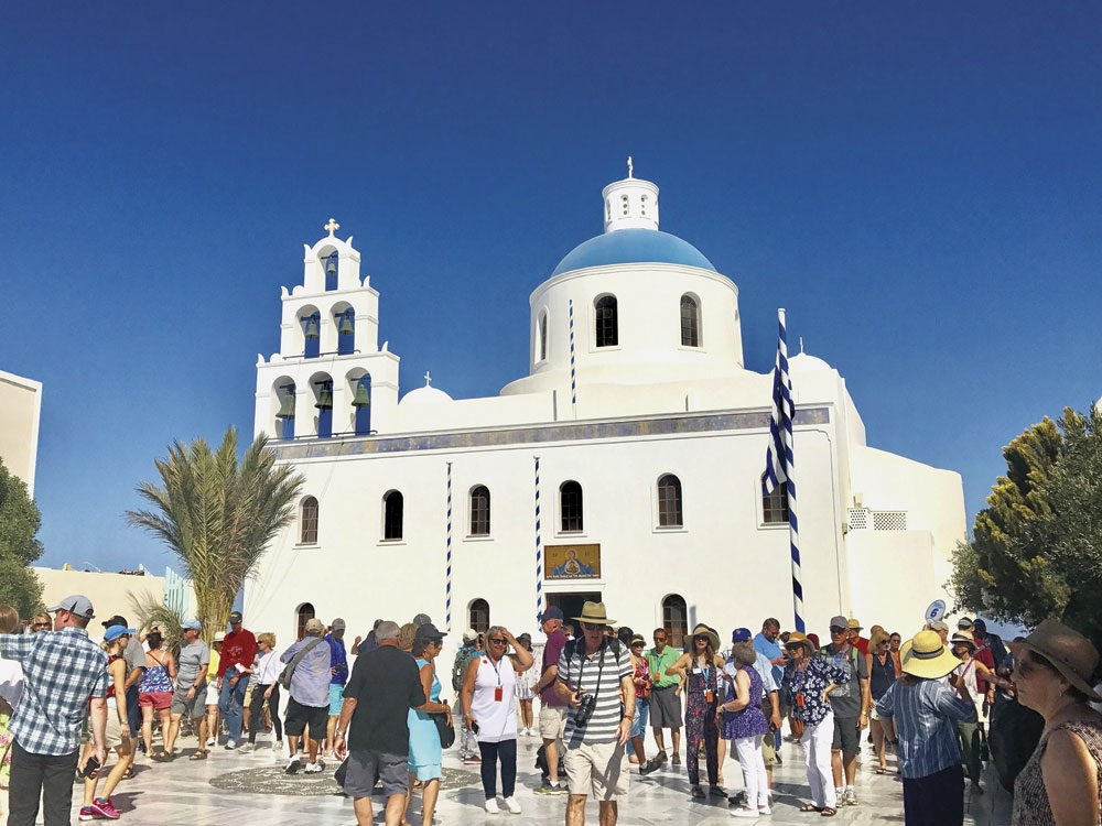 Visitors wander through the streets, hoping to experience Santorini like the locals.