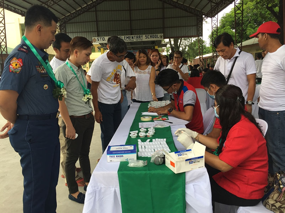 """PAMPANGA. Personnel of the Municipal Health Office facilitate the drug test on appointed officials of Barangay Sto. Niño, San Simon. Looking over are Barangay Captain Perlito """"Dong"""" Dagdag, Jr. and Chief Inspector Louie Gonzaga. (Princess Clea Arcellaz)"""