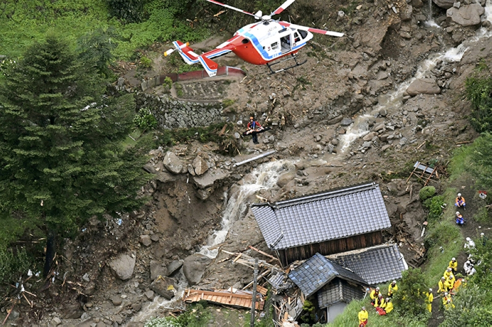 JAPAN. A rescue helicopter hovers over damaged buildings after a landslide caused by heavy rains in Iwakuni, Yamaguchi prefecture, southwestern Japan, Saturday, July 7, 2018. Torrents of rainfall and flooding continued to batter southwestern Japan. (Kyodo News via AP)
