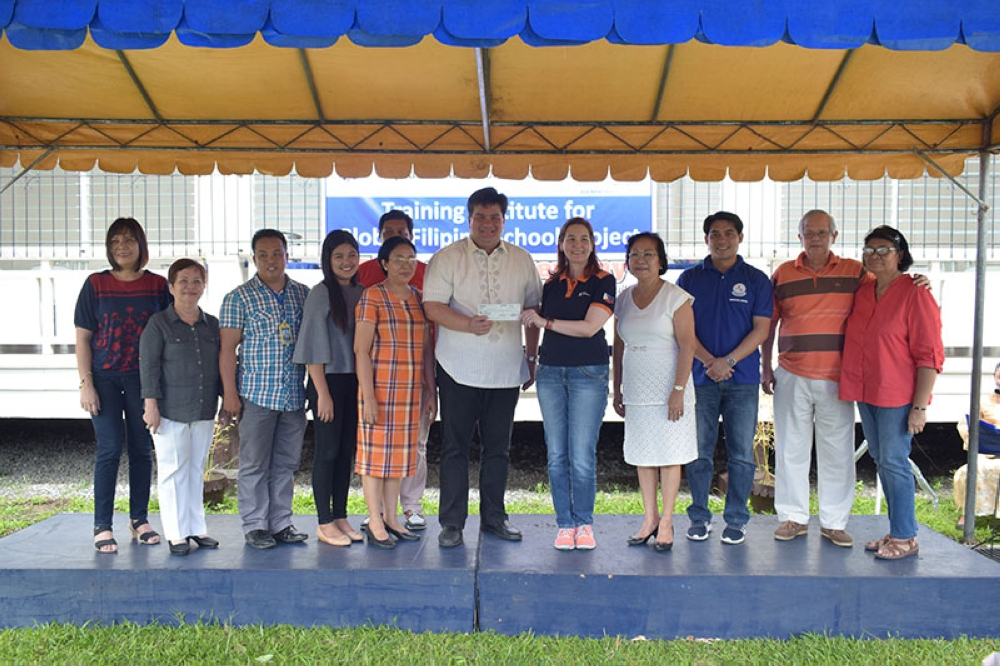 SILAY. Silay City Mayor Mark Golez turns over the check to Joanna Duarte of Ayala Foundation Inc., with the members of the local school board and councilors. (Contributed Photo)