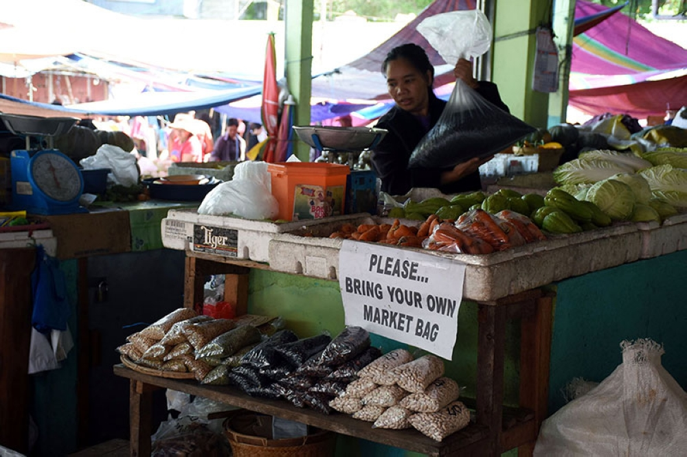 BAGUIO. A stall owner at the Baguio City Market encourages market goers to bring their own plastic containers or eco-bags. (Photo by Redjie Melvic Cawis)