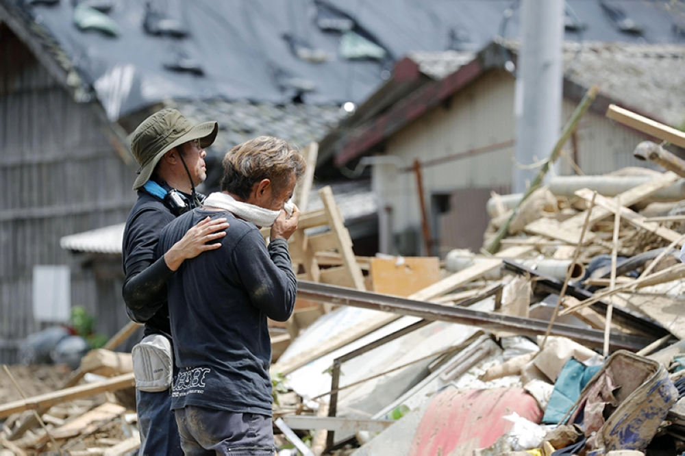 JAPAN. Relatives react to a landslide site where three people were killed, after heavy rain hit southwestern Japan, in Uwajima, Ehime prefecture, Monday, July 9, 2018. (AP)