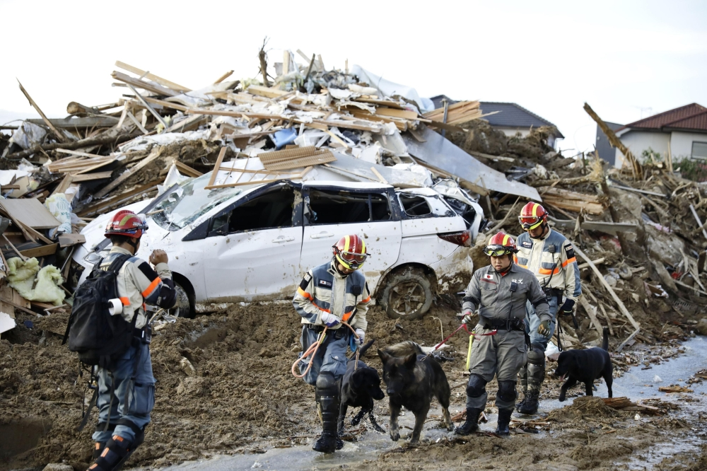 JAPAN. Firefighters with rescue dogs search for missing people after heavy rain hit southwestern Japan, in Kumano town, Hiroshima prefecture, Monday, July 9, 2018. (AP)
