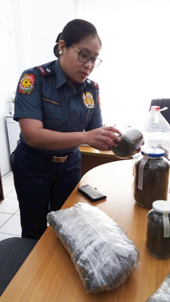 CEBU. Cebu City Police Station 2 Commander Ma. Theresa Macatangay shows the marijuana seeds placed in a bottle. (Photo by Kevin A. Lagunda)