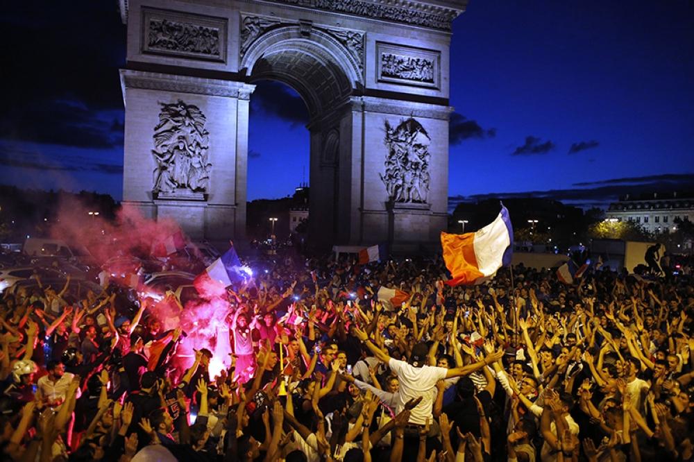 PARIS. People celebrate on the Champs Elysees avenue, with the Arc de Triomphe in background, after the semifinal match between France and Belgium at the 2018 soccer World Cup, Tuesday, July 10, 2018 in Paris. France advanced to the World Cup final for the first time since 2006 with a 1-0 win over Belgium on Tuesday. (AP)