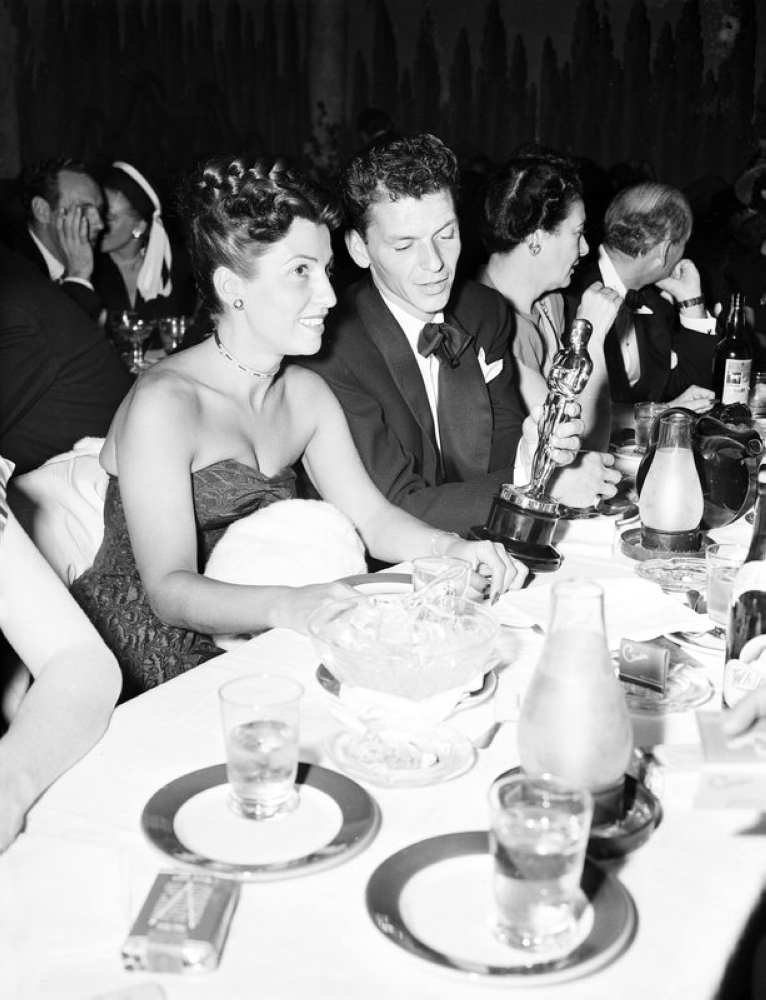 In this March 11, 1946 file photo, at a crowded table at Ciro's, Frank Sinatra steals a glance at his Oscar which he won for his performance in the film