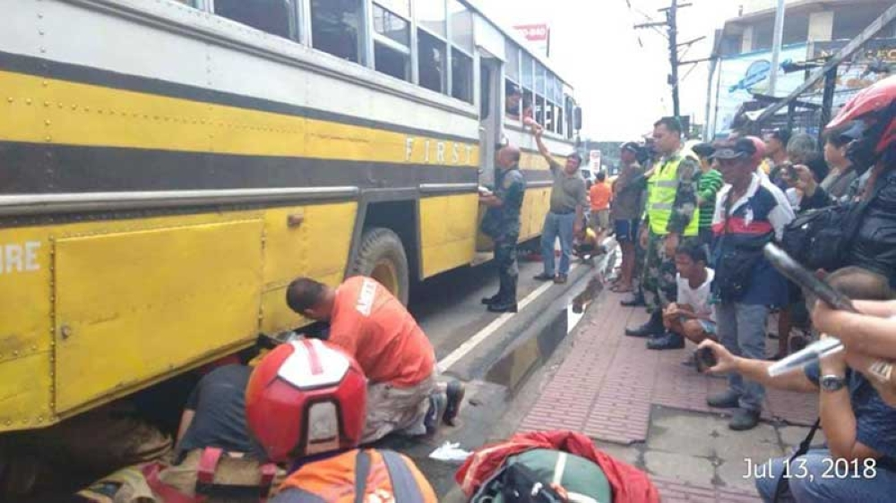 BACOLOD. Rescuers help the woman who went under the bus after she was sideswiped at 15th Lacson Street in Barangay 7, Bacolod City Friday. (Photo by ABS-CBN Bacolod/Mitch Lipa)
