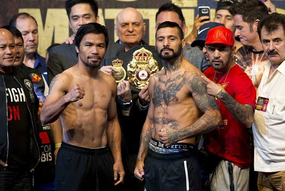 Philippine senator and boxing hero Manny Pacquiao, left, and Argentine World Boxing Association welterweight champion Lucas Matthysse pose after weigh-ins in Kuala Lumpur, Malaysia, Saturday, July 14, 2018. Matthysse and Pacquiao are scheduled to fight on July 15, for the World Boxing Association welterweight title in Malaysia. (AP)