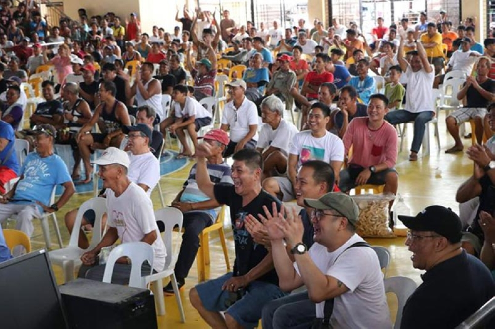 """PORAC. Hundreds of Porac residents and officials led by Vice Mayor Dexter David and Councilors Maynard Lapid and Ludi Muli cheer after Senator Emmanuel """"Manny"""" Pacquiao knocked out his opponent Lucas Matthysse during the WBA Welterweight Championship bout Sunday, July 15. Free wide screen viewing was provided by Vice Governor Dennis Pineda. (Chris Navarro)"""