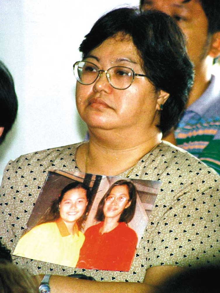 CEBU. Thelma Chiong holds photos of her daughters Jacqueline and Marijoy. The sisters were abducted, raped and murdered. Only Marijoy's body was found. (SunStar File Photo)
