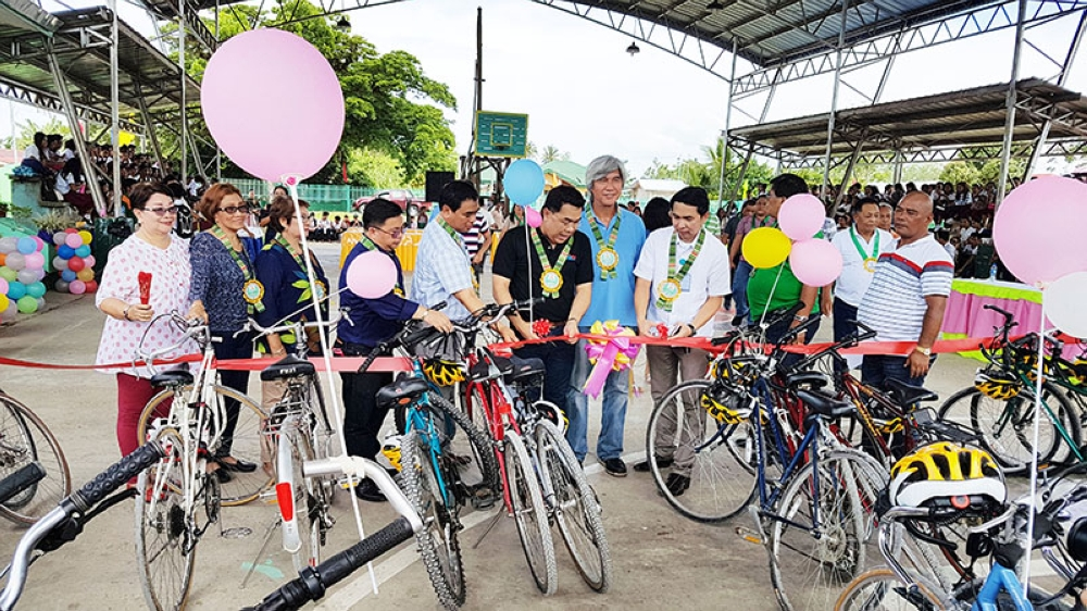 DAVAO. Department of Education Davao regional director Alberto T. Escobarte checks out one of the 40 bicycles while Deped Undersecretary Tonisito Umali and other education officials with Bike for the Philippines founder Joel F. Uichico look on. (Contributed photo)