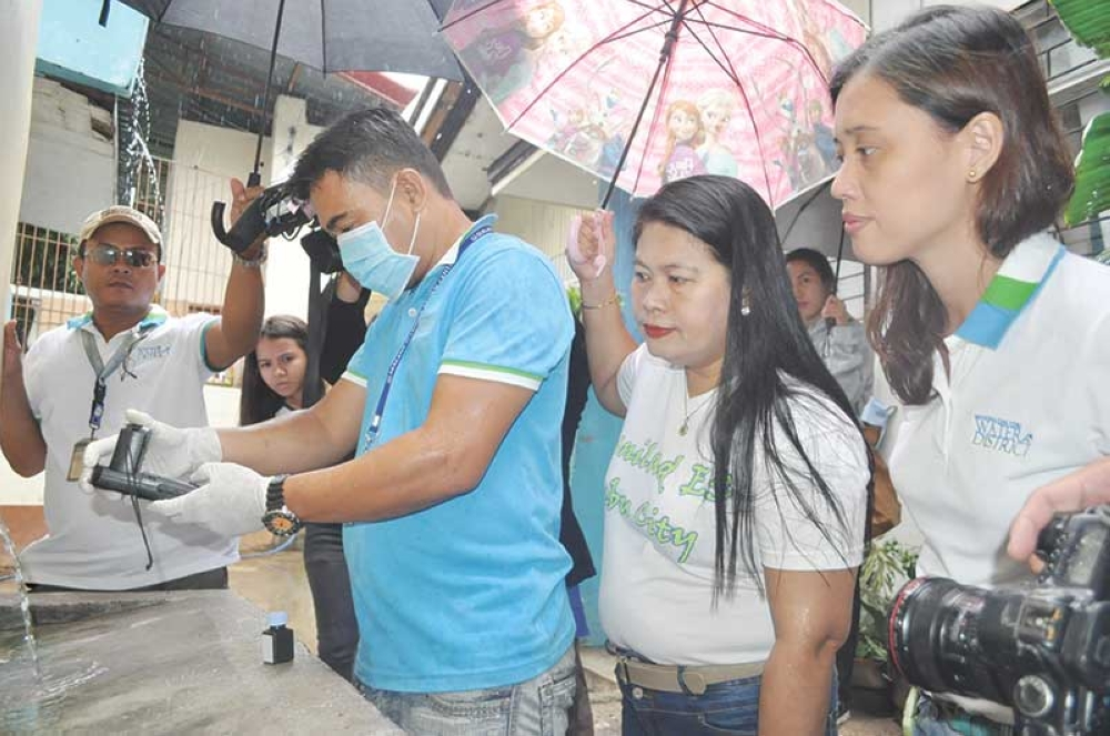 WATER TESTING. Rexie Ragas (third from right) of the MCWD Laboratory gathers a water sample from one of Banilad Elementary School's faucets, while Principal Lily Ann Go (second from right) and MCWD Community Relations Manager Charmaine Kara (right) observe. (Contributed Photo)