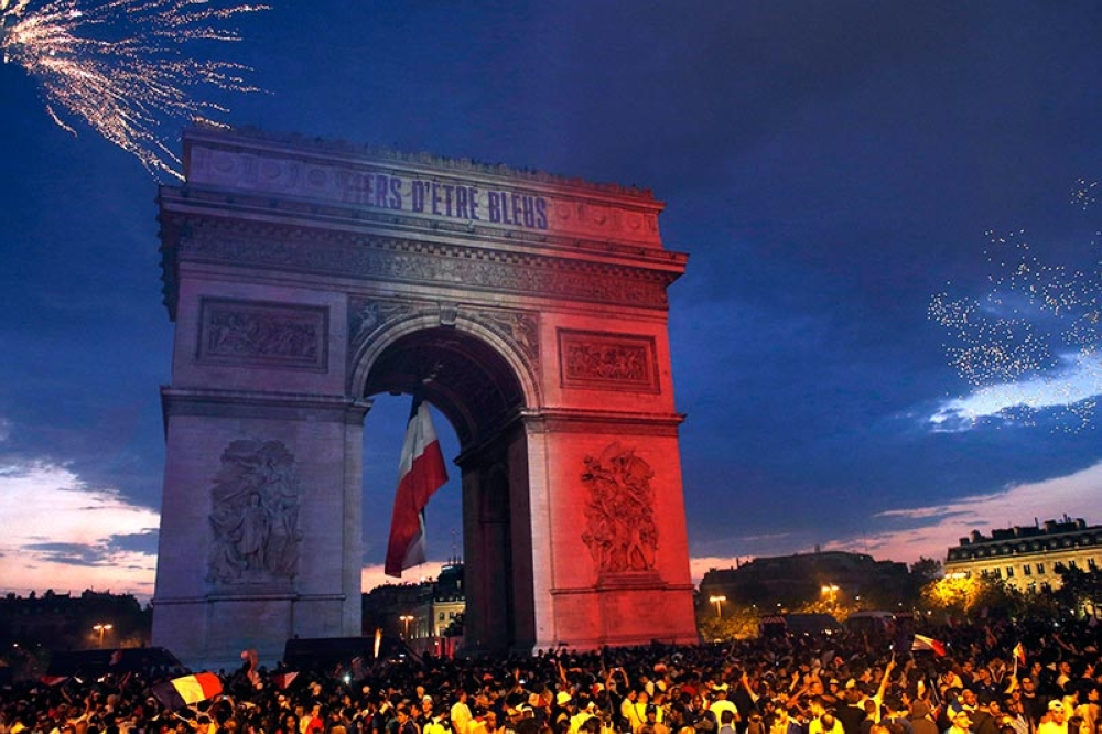 The Arc de Triomphe is illuminated with the colors of the French national flag and by fireworks set off by French soccer fans celebrating France's World Cup victory over Croatia, in Paris, France, Sunday, July 15, 2018. France won the final 4-2. The inscription in French reads : Proud to be blue (French) . <b>(AP Photo)</b>