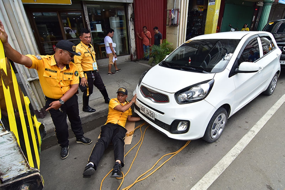 DAVAO. Mga personahe sa Davao City Transport and Traffic Management Office giandam ang sakyanan aron ikarga sa towing truck human mi-parking sa yellow box sa may dalang Ramon Magsaysay, sIyudad sa Davao gahapon sa buntag. (Macky Lim)