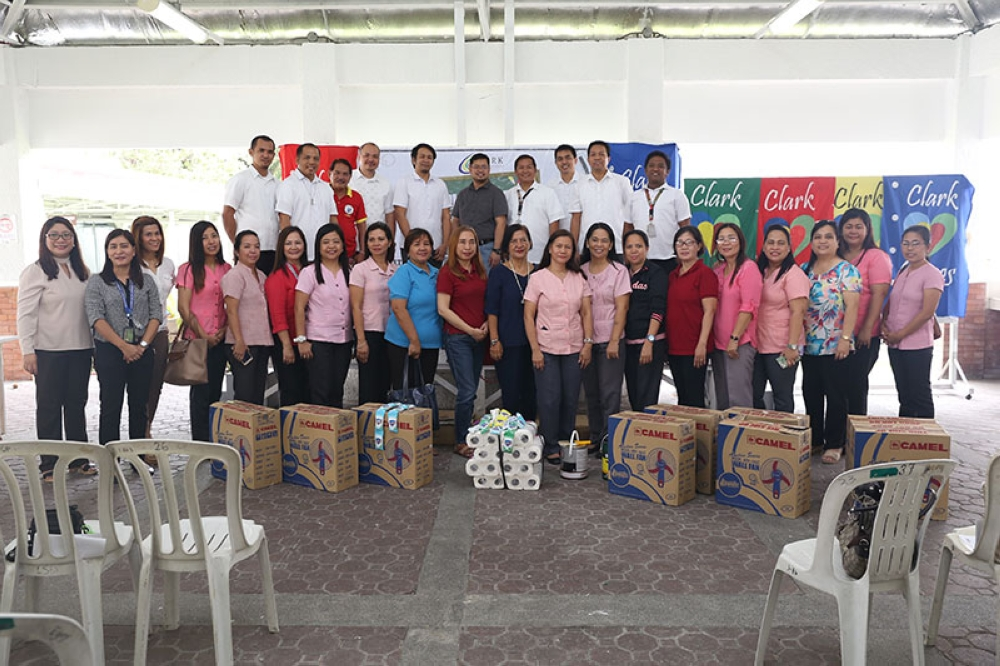 """PAMPANGA. Various beneficiaries of the Clark Development Corporation's (CDC) """"Brigada Eskwela 2018"""" under the Clark Cares Program pose with staff of the CDC-External Affairs Division during the awarding of the distributed items requested by the recipients. (Photo contributed by CDC)"""