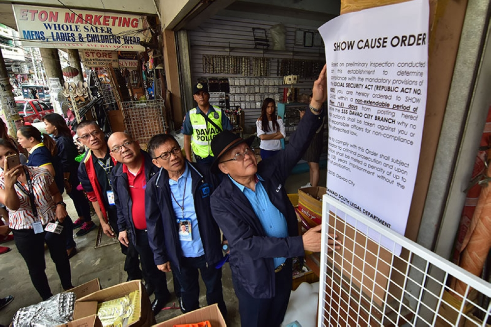 DAVAO. Social Security System (SSS) president and CEO Emmanuel Dooc post a show cause order outside an establishment along Ramon Magsaysay Avenue due to the non-remittance of SSS contributions during an operation Monday, July 16, 2018, inside the Chinatown in Davao City. A total of seven establishments were presented with show cause orders. (Photo by Macky Lim)