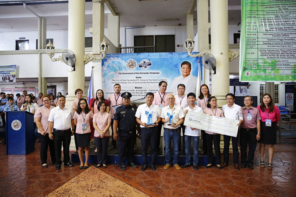 """PAMPANGA. Mayor Edwin """"EdSa"""" Santiago together with Vice-Mayor Jimmy Lazatin, Sangguniang Kabataan Federation president Gustav John Henson and city department heads present the plaques and P20,000 check that the City of San Fernando received for bagging the 2017 Most Successful LGU in the Institutionalization of BPLS Reforms in Central Luzon which was conferred by the Central Luzon Growth Corridor Foundation Inc. during Monday's flag raising rites at city hall. (Photo contributed by CSF-CIO)"""