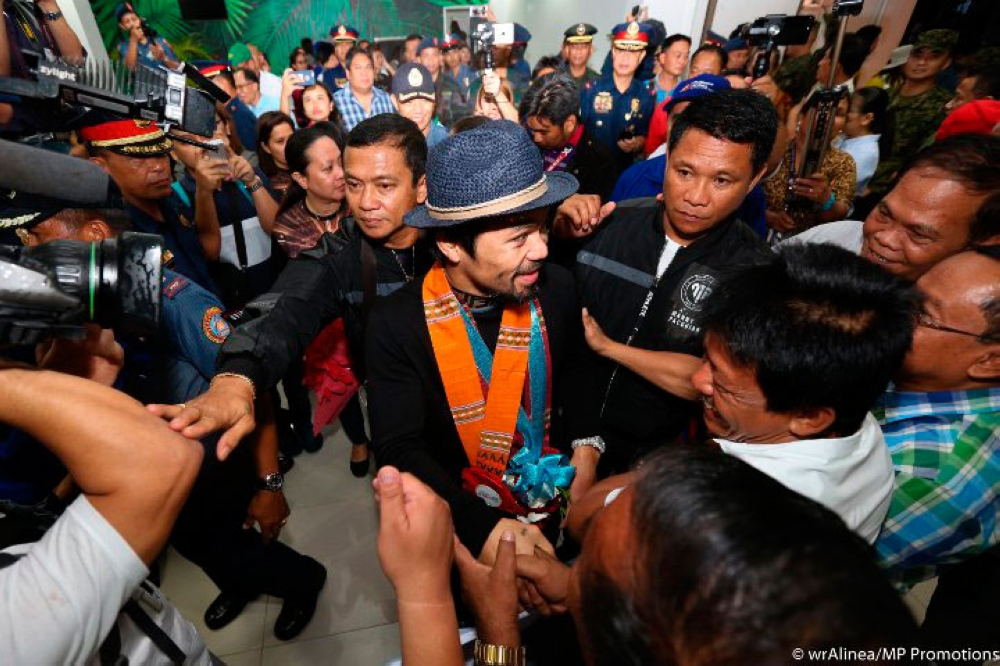 Hero's welcome. Gitapuk-an ang bag-ong WBA welterweight champion Manny Pacquiao (tunga) atol sa iyang pagbalik sa Pilipinas sa miaging adlaw gikan sa malampusong away sa Kuala Lumpur, Malaysia diin iyang gi-TKO sa 7th round si Argentine Lucas Matthysse. (MP Promotions)