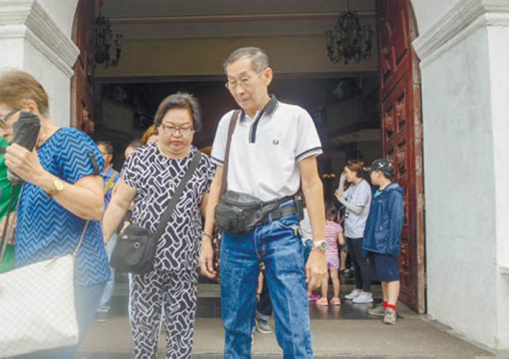 COMMEMORATION. Thelma and Dionisio Chiong leave the Cebu Metropolitan Cathedral after attending a mass commemorating the 21st death anniversary of their daughters. (SunStar Photo / Arni Aclao)