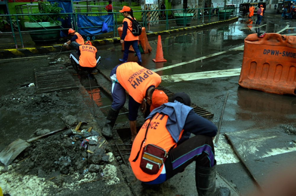 MANILA. Department of Public Works and Highways (DPWH) personnel clean clogged drainage systems in Pasay City on July 18, 2018 in the aftermath of the widespread flooding caused by southwest monsoon rains and Tropical Depression Henry. (Alfonso Padilla/SunStar Philippines)