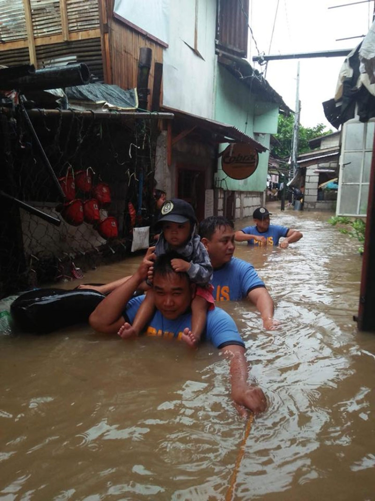 PAMPANGA. A child is carried to safety by members of the Search and Rescue team as PRO-Central Luzon conducts rescue missions in flooded areas in Central Luzon. (PRO-Central Luzon/RPIO)
