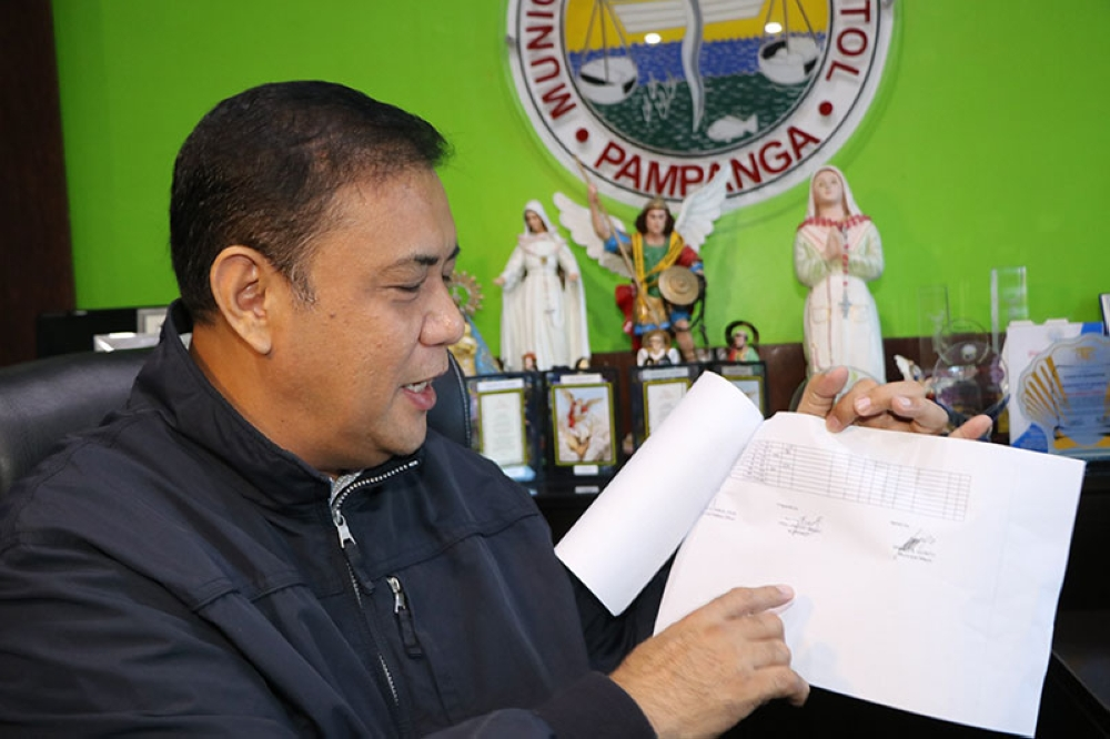 PAMPANGA. Masantol Mayor Danilo Guintu shows a copy of the Municipal Disaster Risk Reduction and Management Council report stating that all 26 barangays in the fourth district town are submerged under floodwaters resulting to a state of calamity Wednesday, July 18, 2018. (Chris Navarro)