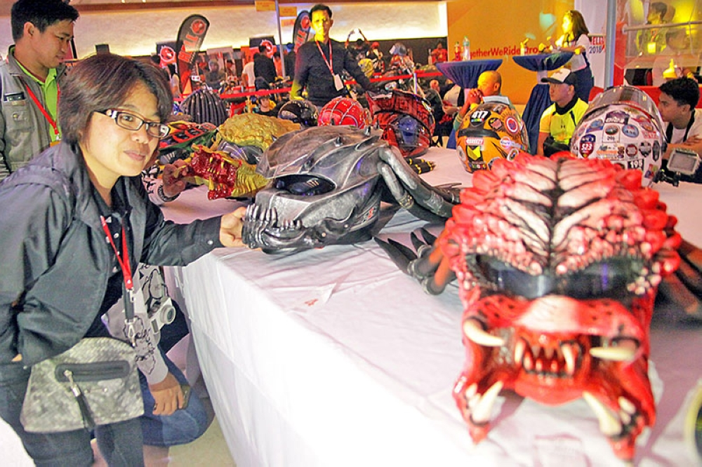 "SCARY. Visitors to a bike fair over the weekend were in awe with the creativity of ""pinoy choppers"" or modified bikes and even helmets on display. Rose Malekchan of DZWT scrutinized further the ""Predator"" inspired head gears. (JJ Landingin)"