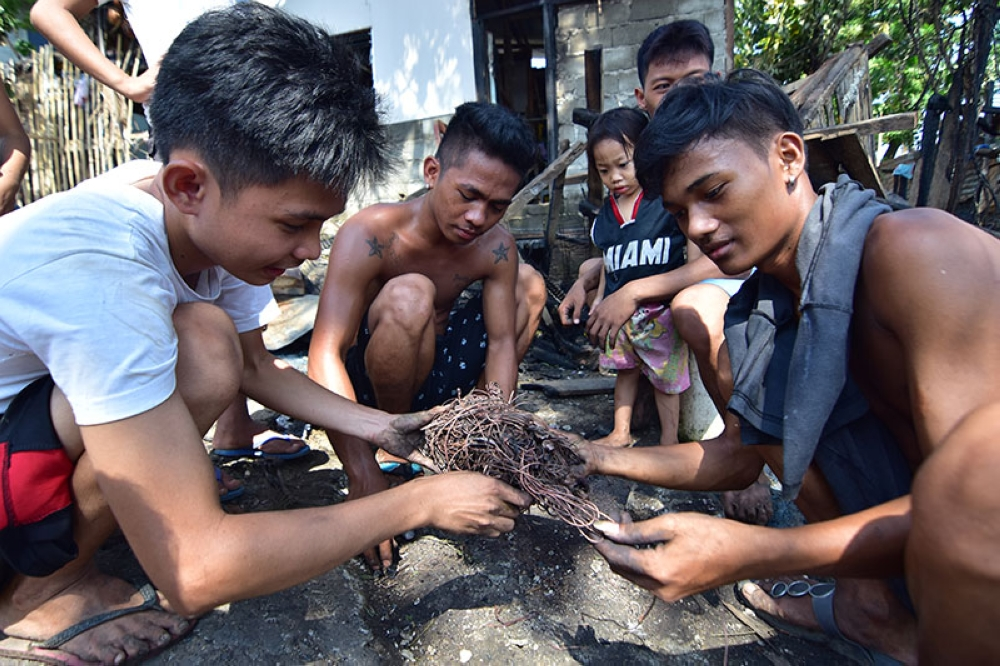 DAVAO. Three men tangle a copper wire as they say can be sold for P360 per kilo in a nearby junk shop and the money will be used to buy rice for their families after their houses was razed by the fire Wednesday morning, July 18, 2018 in Malanding, KM 11 Sasa in Davao City. (Photo by Macky Lim)