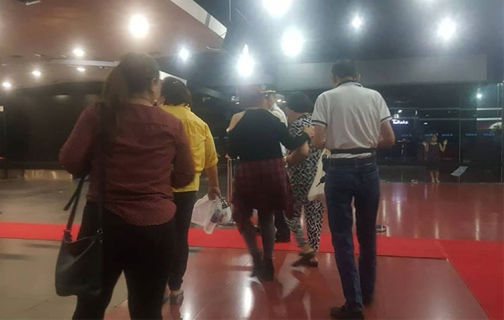 CEBU. Thelma Chiong, mother of the late Jacqueline and Marijoy Chiong, is escorted out of the theater. She was emotional when she saw the brutal rape scenes of the movie