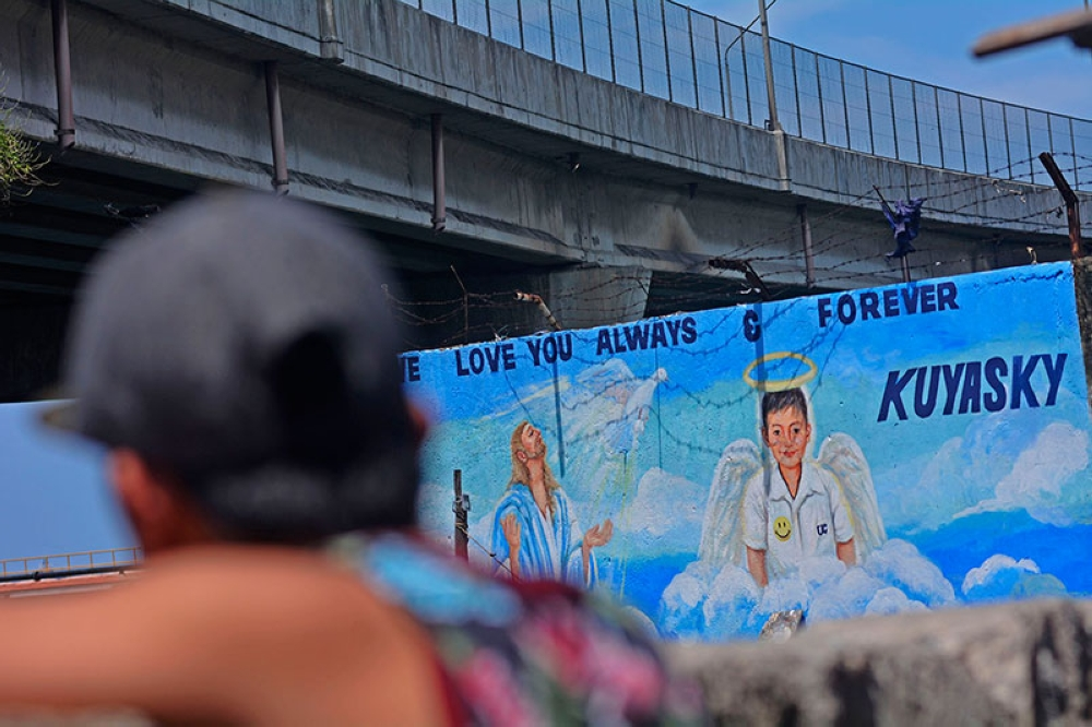 CEBU. Mark Abatayo looks at a mural that portrays his son Skyler as an angel next to Jesus. (Amper Campaña)
