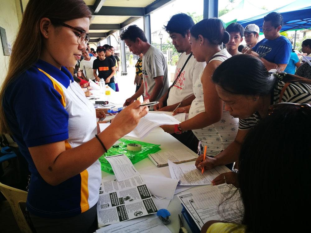Mandaue's social welfare team distributes cash to participants of the unconditional cash transfer program (SunStar Foto/Allan Cuizon)
