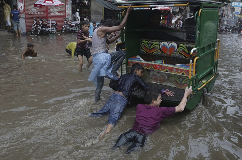 PAKISTAN. Pakistani children play in flooded street following heavy rain in Lahore, Pakistan, Friday, July 20, 2018. (AP)